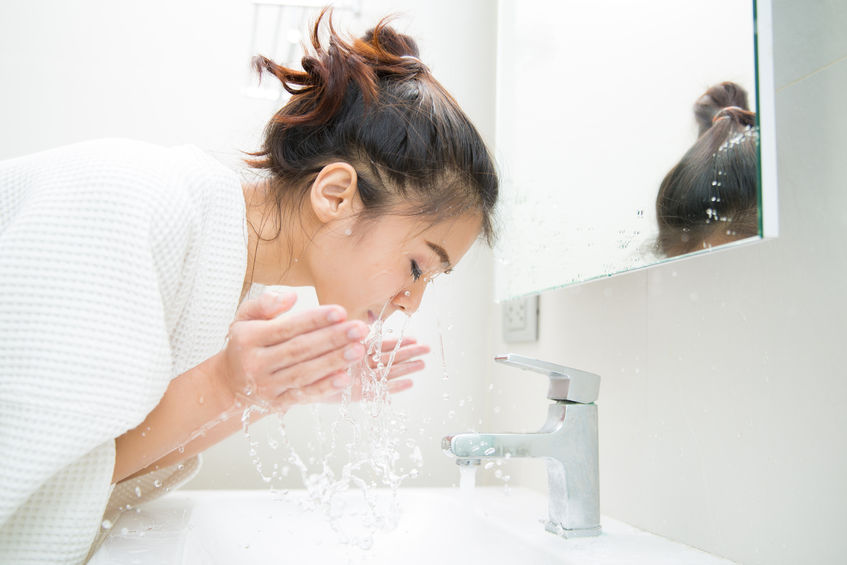 girl with acne washing her face using Acne Intelligence for clearer skin