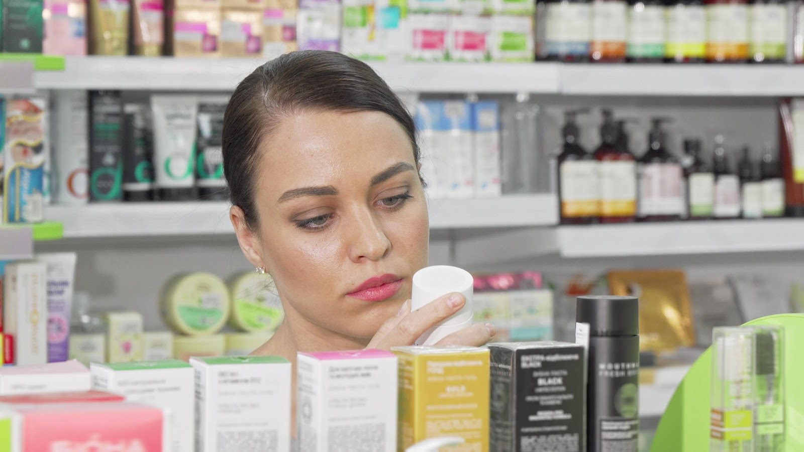 woman looking at acne-fighting products including ahas and bhas